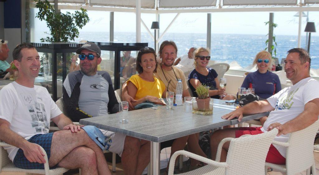 żeglarze siedzący w restauracji w marinie po zajęciach żeglarskich