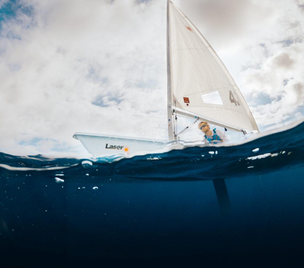 a boy sailing a laser 4.7 dinghy in tenerife
