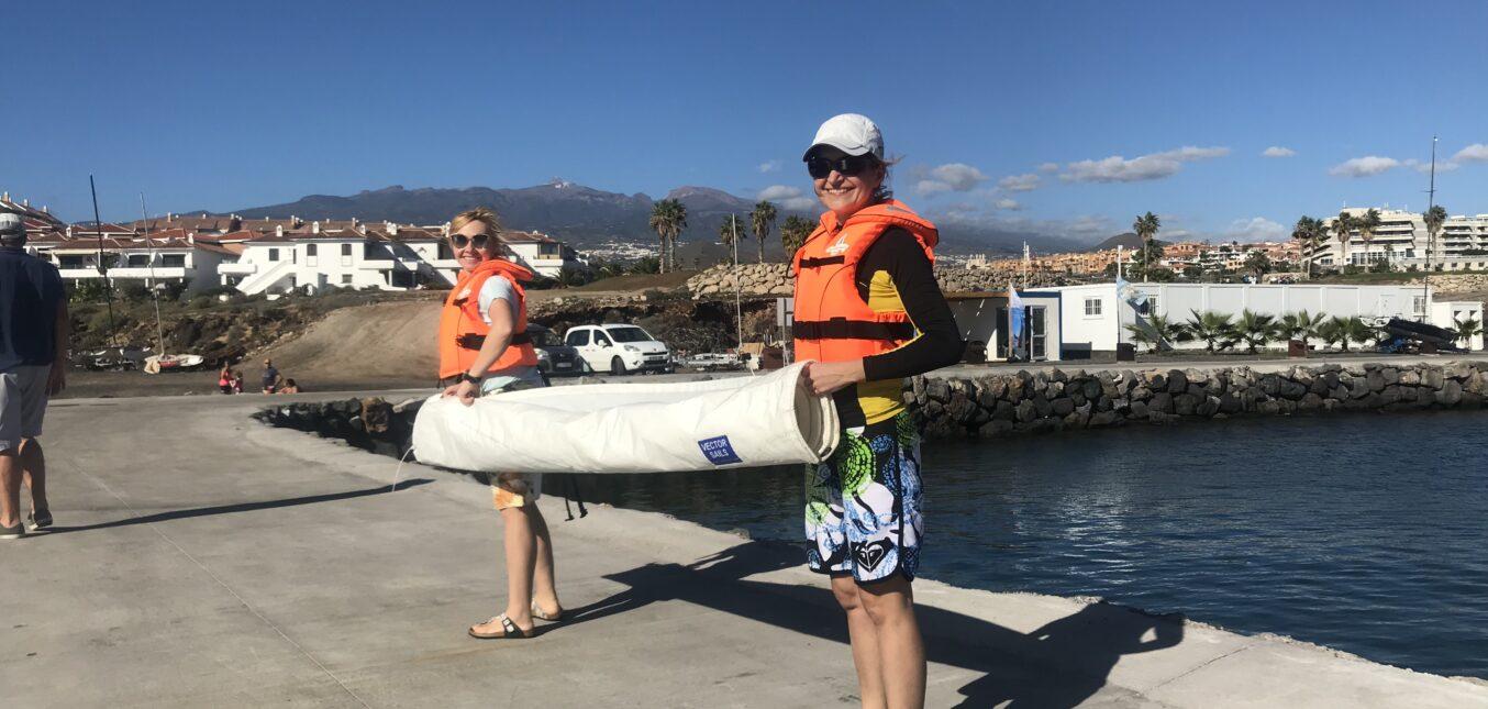 Kursantki niosą żagiel do bazy Amarilla Sailing Club na Teneryfie